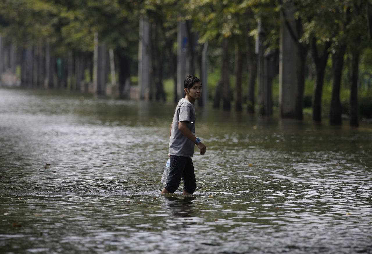 A Thai resident crosses a flooded street in Bangkok, Thailand, Saturday, Nov. 5, 2011. Floodwaters lapped Bangkok's largest outdoor market Saturday as officials warned that no major barriers now stood in the way to prevent the water from reaching the heart of the Thai capital. (AP Photo/Aaron Favila)