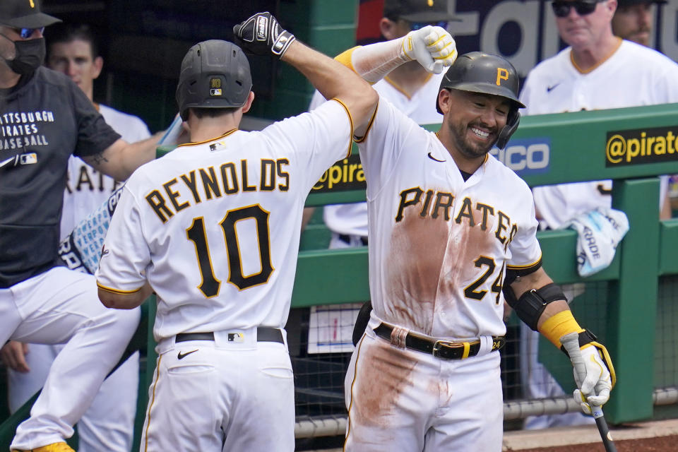 Pittsburgh Pirates' Bryan Reynolds, left, celebrates with Phil Evans as he returns to the dugout after hitting a two-run home run off Los Angeles Dodgers starting pitcher Julio Urias during the third inning of a baseball game in Pittsburgh, Thursday, June 10, 2021. (AP Photo/Gene J. Puskar)