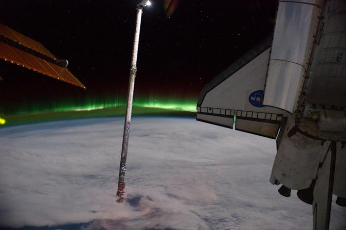 This panoramic view provided by NASA was photographed from the International Space Station, looking past the docked space shuttle Atlantis' cargo bay and part of the station including a solar array panel toward Earth, was taken on July 14, 2011 as the joint complex passed over the southern hemisphere. Aurora Australis or the Southern Lights can be seen on Earth's horizon and a number of stars are visible also. (AP Photo/NASA)