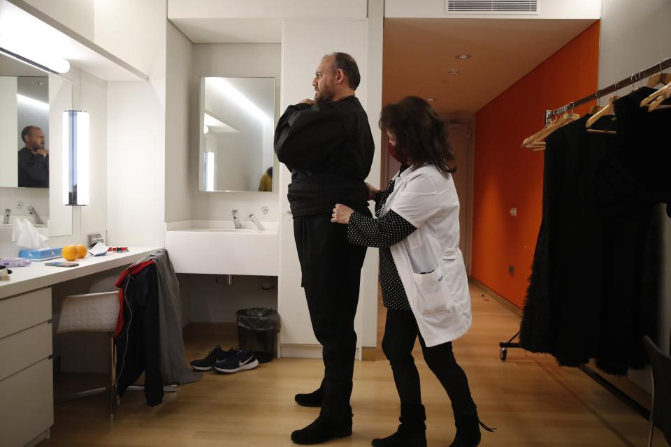 """Dresser Eleni Laskari, right, adjusts tenor Dimitris Paksoglou's Greek traditional costume before the rehearsal of """"Despo-Greek Dances"""" Opera and dance performance in Athens, Thursday, March 4, 2021. Dozens of museum exhibitions, theater productions, discussion panels and historical re-enactments were planned in Greece for this year to commemorate the bicentennial of the 1821-1832 Greek War of Independence. But due to the coronavirus pandemic, mezzo-soprano Artemis Bogri and her fellow singers stepped onstage in an empty theater to perform the Greek National Opera's new production of """"Despo,"""" one of the events marking 200 years since the war that resulted in Greece's independence from the Ottoman Empire and rebirth as a nation. (AP Photo/Thanassis Stavrakis)"""