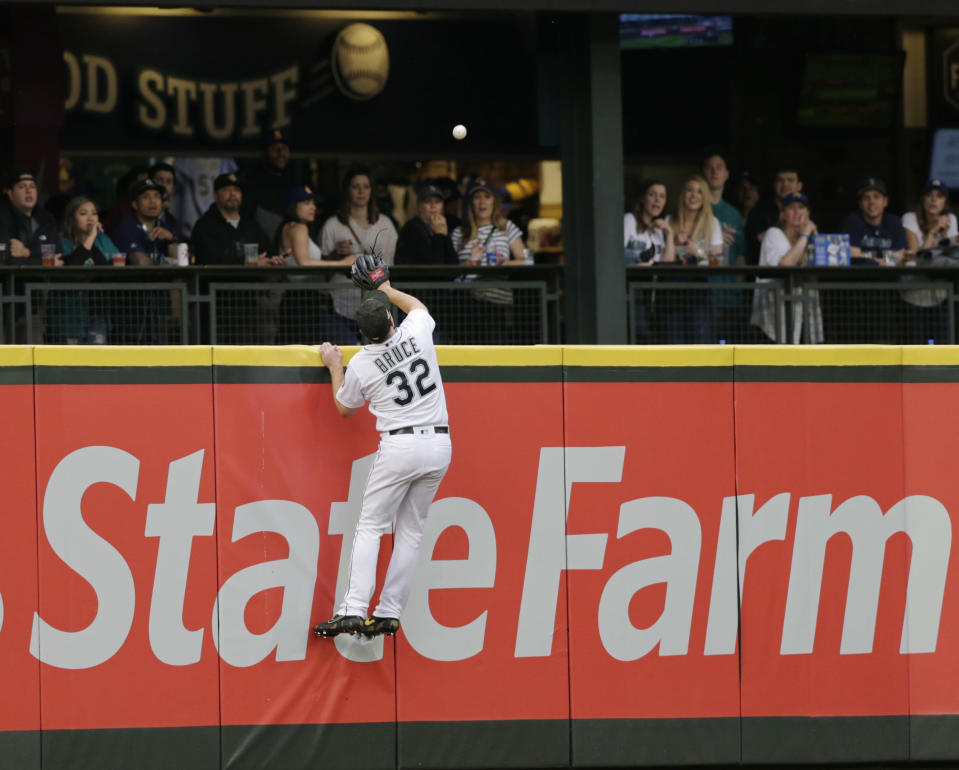 Seattle Mariners left fielder Jay Bruce leaps at the wall in vain for a home run by Minnesota Twins' C.J. Cron during the second inning of a baseball game Saturday, May 18, 2019, in Seattle. (AP Photo/John Froschauer)