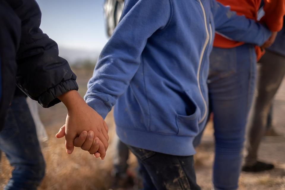 Asylum seeking unaccompanied minors hold hands as they await transport after crossing the Rio Grande river into the United States from Mexico on a raft in Penitas, Texas, on March 12, 2021. The unrelated minors are all from Honduras.   (Adrees Latif/Reuters)