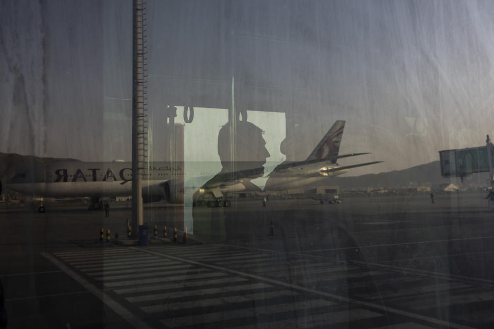 A Qatar Airways aircraft is reflected on a bus at the airport in Kabul, Afghanistan, Thursday, Sept. 9, 2021. Some 200 foreigners, including Americans, flew out of Afghanistan on an international commercial flight from Kabul airport on Thursday, the first such large-scale departure since U.S and foreign forces concluded their frantic withdrawal at the end of last month. (AP Photo/Bernat Armangue)