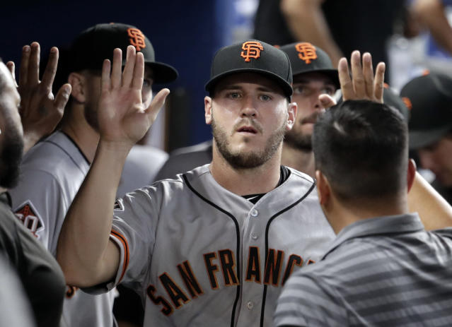 San Francisco Giants relief pitcher Ty Blach is congratulated in the dugout after being relieved in the 16th inning of a baseball game against the Miami Marlins, Thursday, June 14, 2018, in Miami. The Giants won 6-3 in 16 innings. (AP Photo/Lynne Sladky)
