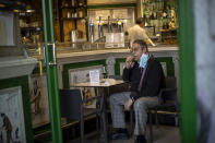 A customer sits inside of a bar in downtown Madrid, Spain, Friday, Oct. 9, 2020. Spanish Prime Minister Pedro Sánchez is holding a Cabinet meeting to consider declaring a state of emergency for Madrid in order to impose stronger anti-virus restrictions on reluctant regional authorities. (AP Photo/Manu Fernandez)