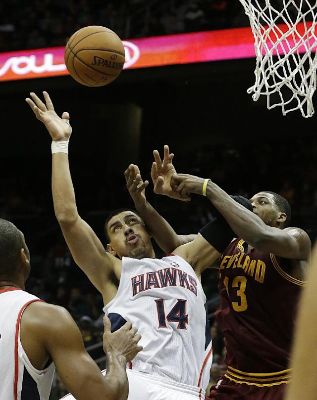 Atlanta Hawks power forward Gustavo Ayon (14) and Cleveland Cavaliers' Tristan Thompson fight for a rebound in the second half of an NBA basketball game Friday, Dec. 6, 2013, in Atlanta. (AP Photo/John Bazemore)
