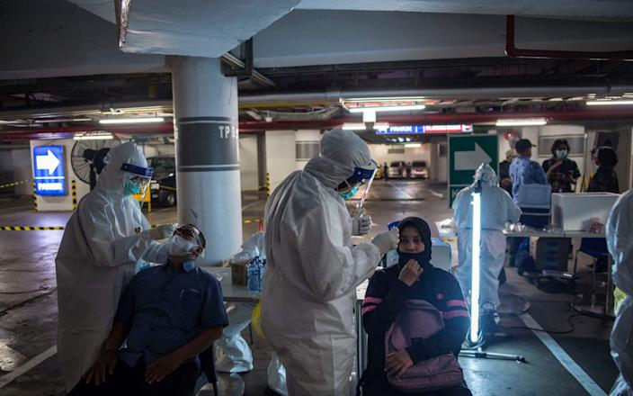 In Surabaya, Indonesia, health workers collect swab samples from shoppers to test for Covid-19 before they are allowed to enter a shopping mall - Juni Kriswanto / AFP