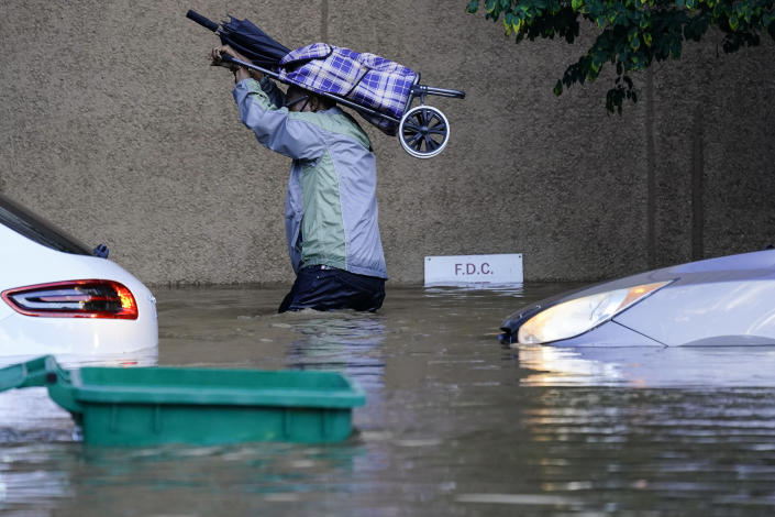 A resident waist-deep in floodwaters in Philadelphia on Thursday, passing submerged cars.