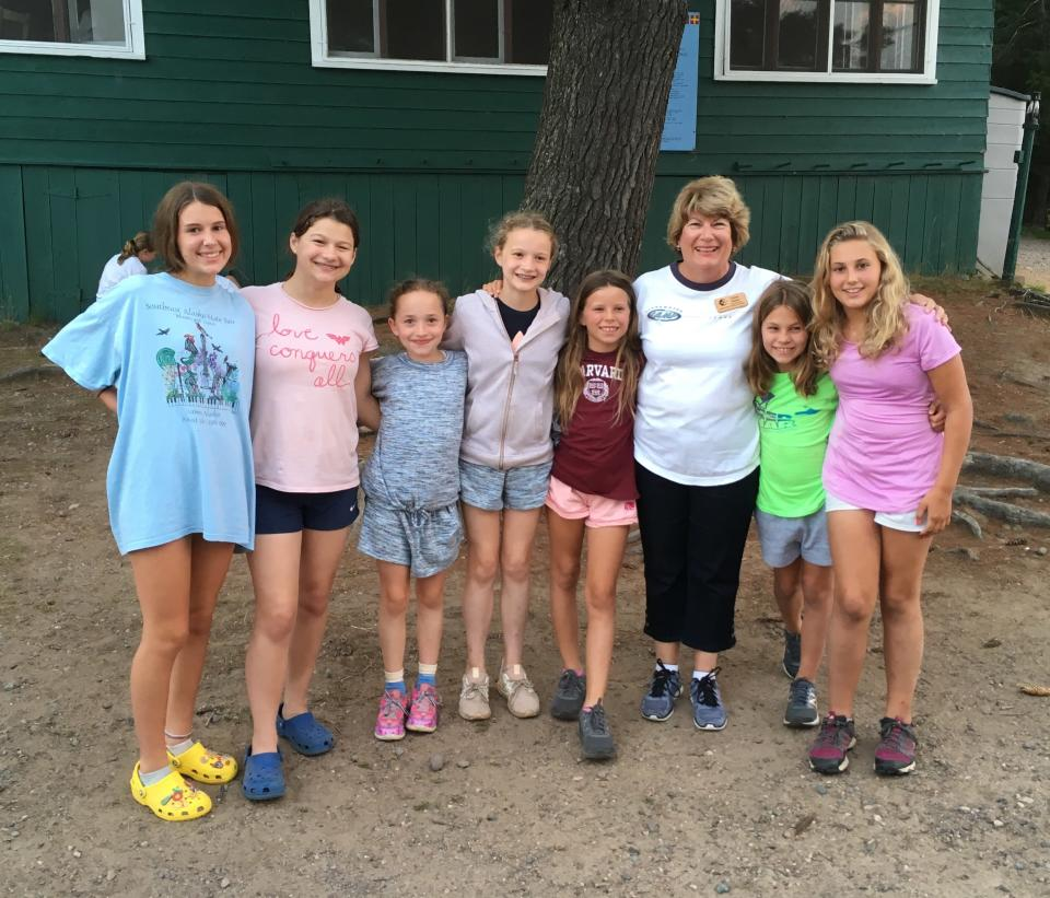 This July 2019 photo provided by Clearwater Camp shows Clare Crawford, left, Elizabeth Crawford, Cecily Crawford, Charlotte Crawford, Ella Wester, Carol Vance, Drennen Wester and Lexi Schneider at Clearwater Camp in Minocqua, Wis. In some families, summer camp is an experience passed down over generations. Grandparents and grandkids can reminisce about camp traditions that seem timeless. Parents who had formative experiences at camp want the same for their kids. (Clearwater Camp via AP)
