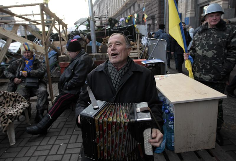 A man plays accordion during a Pro-European Union rally in Independence Square in Kiev, Ukraine, Monday, Dec. 23, 2013. Ukraine has been stricken with mass protests for over a month. Protesters are demanding President Viktor Yanukovych's resignation over his decision to ditch a pact with the European Union in favor of closer ties with Russia. (AP Photo/Sergei Chuzavkov)