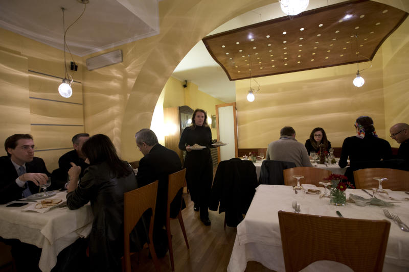 Restaurant owner Patrizia Podetti, center, serves dishes in her Velando restaurant, in Rome, Monday, March 18, 2013. Velando is a favorite dining spot for churchmen, with sleek wooden furnishings, subdued lighting and vaulted, whitewashed ceiling giving an air of a church sacristy. Joseph Ratzinger, recently retired Pope Benedict XVI, often dined there before becoming pope. (AP Photo/Andrew Medichini)