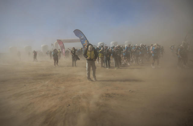 A sandstorm sweeps across as competitors take part in the 33rd edition of Marathon des Sables, in the Sahara desert, near Merzouga, southern Morocco, Saturday, April 14, 2018. The 33rd edition of the annual race, considered to be one of the most demanding ultramarathons in the world, finished Saturday after six grueling days and about 250 kilometers (150 miles). (AP Photo/Mosa'ab Elshamy)