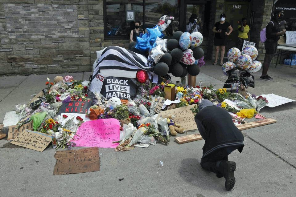 People gather and pray around a makeshift memorial honouring George Floyd.