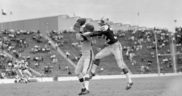 FILE - In this Oct. 16, 1960, file photo, Cleveland Browns' Ray Renfro (26), left, catches a pass before being tackled by Dallas Cowboys' Tom Franckhauser (32), right, during the first half of a football game at the Cotton Bowl in Dallas. George Halas wanted an NFL team in Dallas, and in 1960 the influential founder of the Chicago Bears helped Clint Murchison get one. (AP Photo/File)
