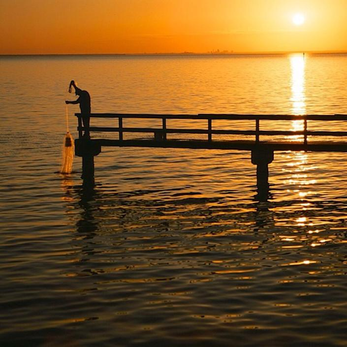 <p>Casting a net off a pier on the Mobile Bay Basin. (Photo: Mobile Baykeeper Swimmable Water Weekend Photo Contest) </p>