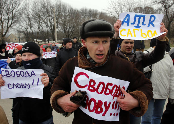 """Crimean Tatars shout slogans and hold banners which reads: """"Freedom of speech"""" during the pro-Ukraine rally in Simferopol, Crimea, Ukraine, Monday, March 10, 2014. Russian President Vladimir Putin on Sunday defended the separatist drive in the disputed Crimean Peninsula as in keeping with international law, but Ukraine's prime minister vowed not to relinquish """"a single centimeter"""" of his country's territory. The local parliament in Crimea has scheduled a referendum for next Sunday.(AP Photo/Darko Vojinovic)"""