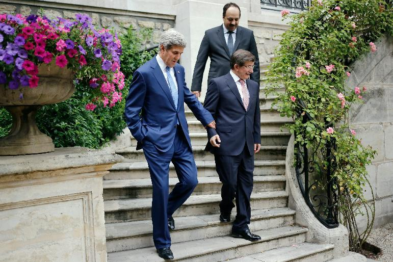 US Secretary of State John Kerry (L) speaks with Turkish Foreign Minister Ahmet Davutoglu (R) and Qatari Foreign Minister Khaled al-Attiyah (up), as they walk down a staircase at the Turkish ambassador's residence in Paris, on July 26, 2014