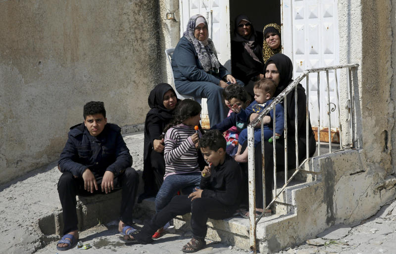 In this Wednesday, March 27, 2019 photo, relatives of Palestinian groom Walid al-Shawa, sit in front of the rubble of a building that was destroyed in an Israeli airstrike Monday, in Gaza City. Al-Shawa was due to get married in two weeks, but an Israeli airstrike on a Gaza City building destroyed his sister's apartment, where he had rented a second floor bedroom and had amassed everything he and his bride needed for the wedding. (AP Photo/Adel Hana)