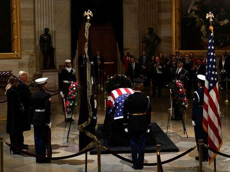 US President Donald Trump and his wife Melania Trump arrive to pay their respects to former US President George H. W. Bush as he lies in state in the US Capitol's rotunda in Washington