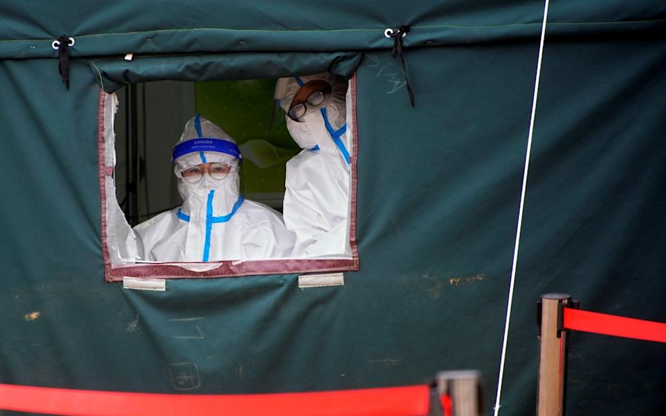 Medical workers in protective suits wait to collect swabs from rescue workers to test for Covid - Reuters