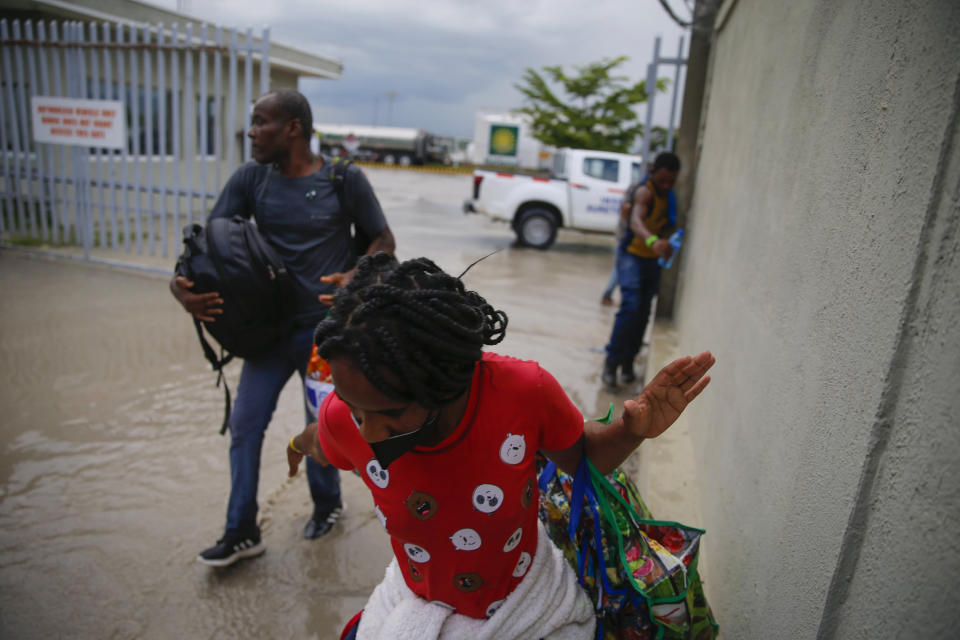 Haitians deported from the United States leave Toussaint Louverture International Airport under a rain shower in Port au Prince, Haiti, Sunday, Sep. 19, 2021. Thousands of Haitian migrants have been arriving to Del Rio, Texas, to ask for asylum in the U.S., as authorities begin to deported them to back to Haiti. (AP Photo/Joseph Odelyn)