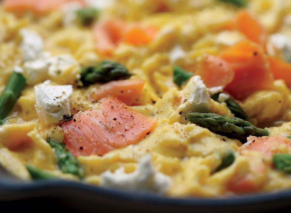 Healthy scrambled eggs with salmon asparagus and goat cheese