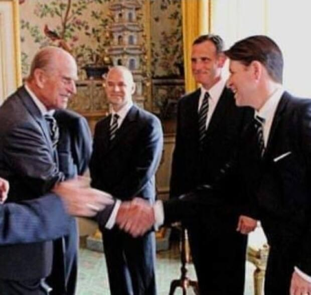 Christian Corbet shaking hands with Prince Philip.