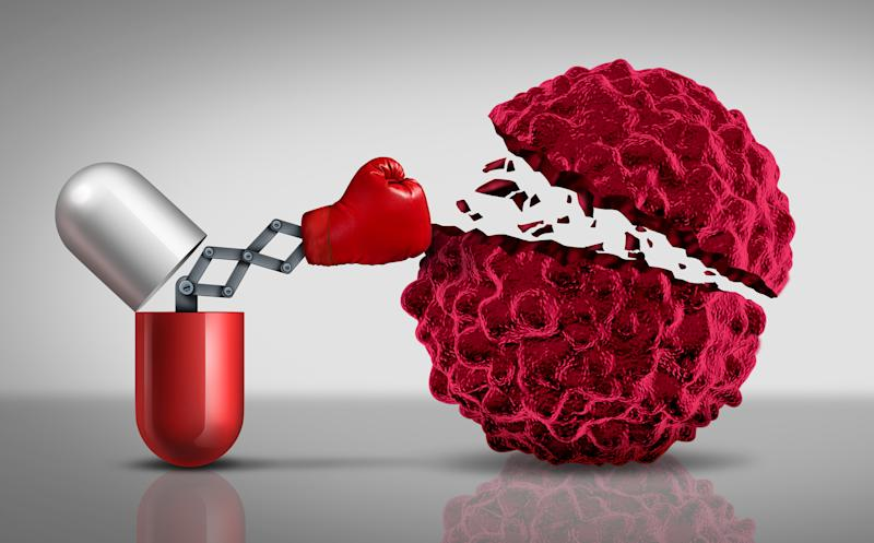 Boxing glove on a mechanical arm extending from a capsule to hit a cancer cell.