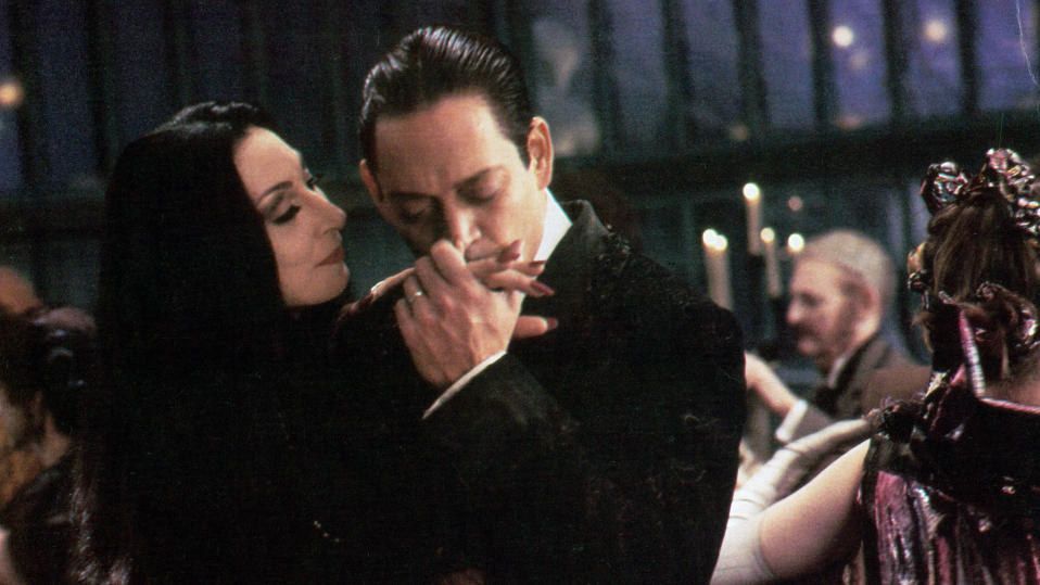 Anjelica Huston is kissed by Raul Julia in a scene from the film 'The Addams Family', 1991. (Photo by Orion/Getty Images)