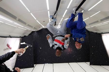 """Retired sprinter Usain Bolt and French astronaut Jean-Francois Clervoy, CEO of Novespace, are spayed with champagne from a bottle of """"Mumm Grand Cordon Stellar"""" designed by French Interior designer Octave de Gaulle as they enjoy zero gravity conditions during a flight in a specially modified Airbus Zero-G plane above Reims, France, September 12, 2018. REUTERS/Benoit Tessier"""