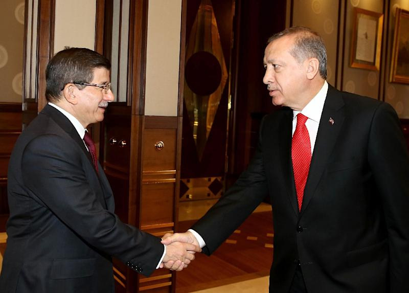 Turkey's President Recep Tayyip Erdogan (R) shakes hands with prime minister and leader of Justice and Development Party Ahmet Davutoglu in Ankara on August 24, 2015, in an image made available by Turkish presidential press service (AFP Photo/)