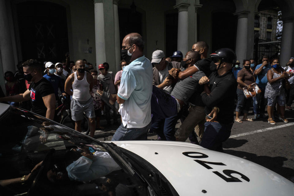 Police detain an anti-government demonstrator during a protest in Havana, Cuba, Sunday July 11, 2021. Hundreds of demonstrators went out to the streets in several cities in Cuba to protest against ongoing food shortages and high prices of foodstuffs, amid the new coronavirus crisis. (AP Photo/Ramon Espinosa)