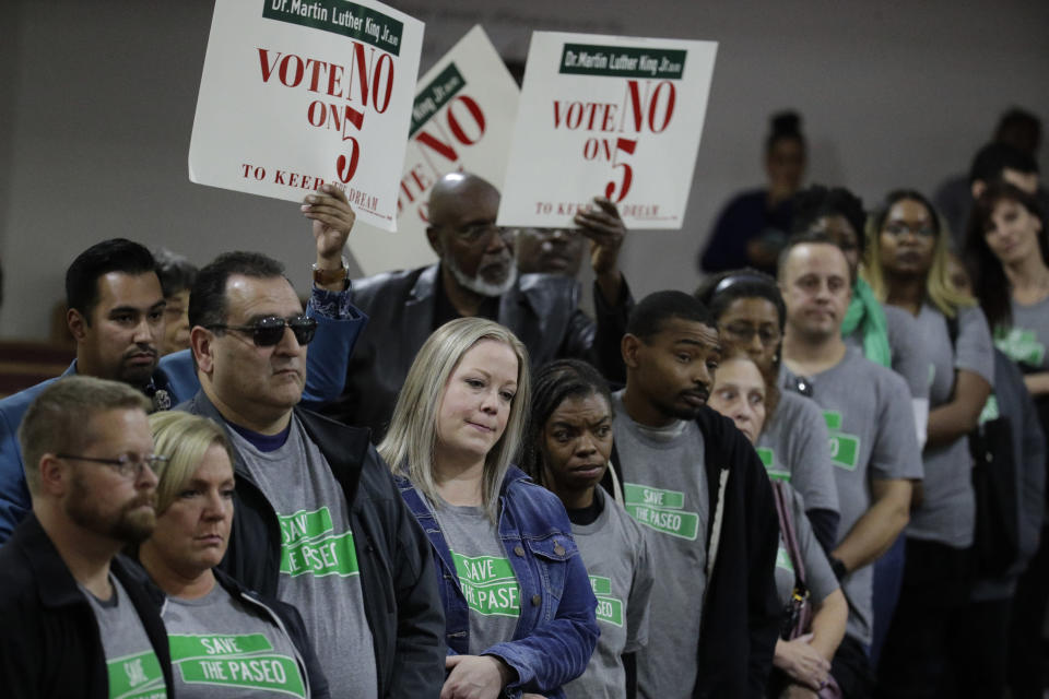 "In this Sunday, Nov. 3, 2019, photo, people wearing ""Save The Paseo"" shirts stand among attendees at a rally to keep a street named in honor of Dr. Martin Luther King Jr. at the Paseo Baptist Church in Kansas City, Mo. In January, the City Council voted to rename one of the city's main boulevards, The Paseo, after King, but many in the community want the old name back. A petition drive put the issue on the Nov. 5 ballot pitting neighbors against each other. (AP Photo/Charlie Riedel)"