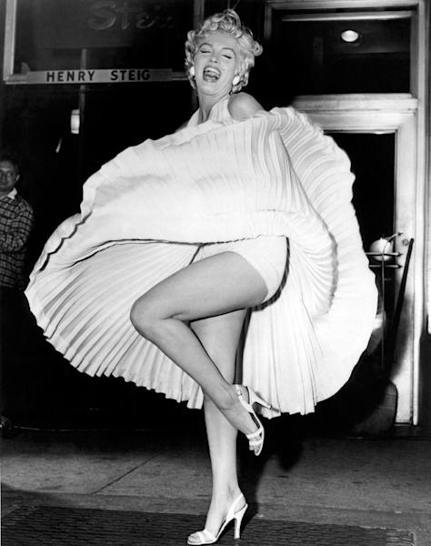 "FILE - In this September 15, 1954 publicity photo courtesy Running Press, Marilyn Monroe is shown during the ""subway"" scene of ""The Seven Year Itch,"" filmed late in the evening on Lexington Avenue in New York City. It required several retakes in front of over two thousand gawking spectators and reporters. The picture is included in a new 2012 book, ""Marilyn in Fashion,"" published by Running Press. (AP Photo/Courtesy Running Press, File)"
