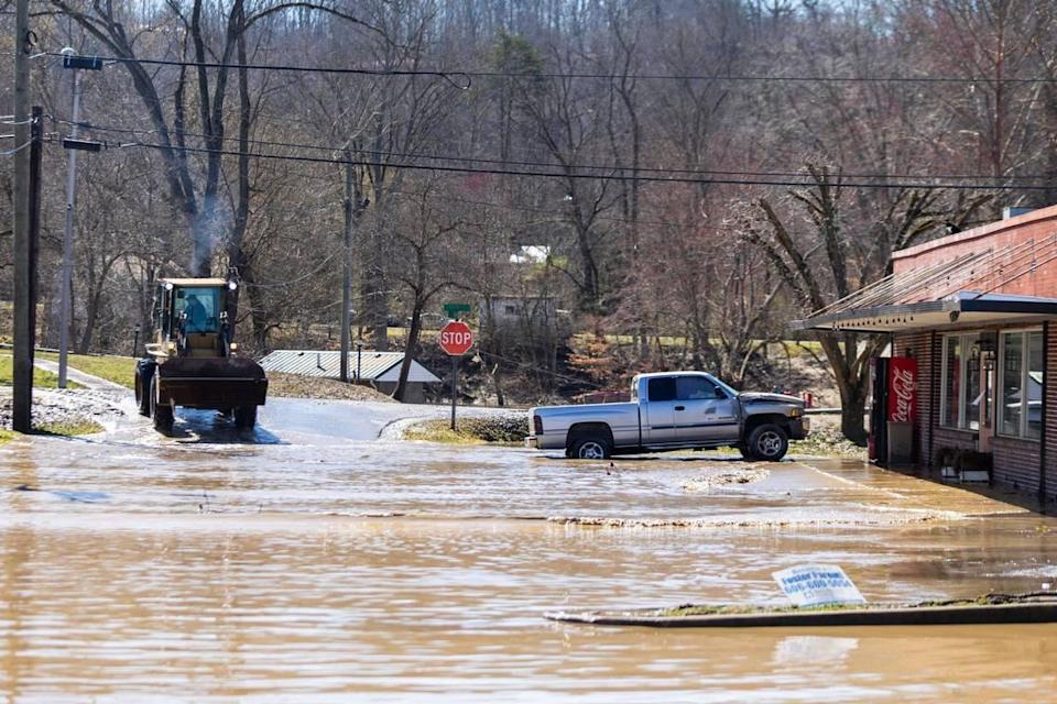 A utility vehicle works to remove water and mud from Lumber Street after severe flooding in downtown in Beattyville Ky., Wednesday, March 3, 2021.
