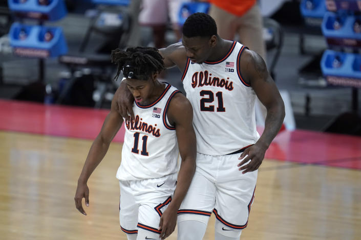 Illinois center Kofi Cockburn (21) talks with Illinois guard Ayo Dosunmu (11) after a foul against Loyola Chicagoduring the second half of a men's college basketball game in the second round of the NCAA tournament at Bankers Life Fieldhouse in Indianapolis, Sunday, March 21, 2021. (AP Photo/Paul Sancya)