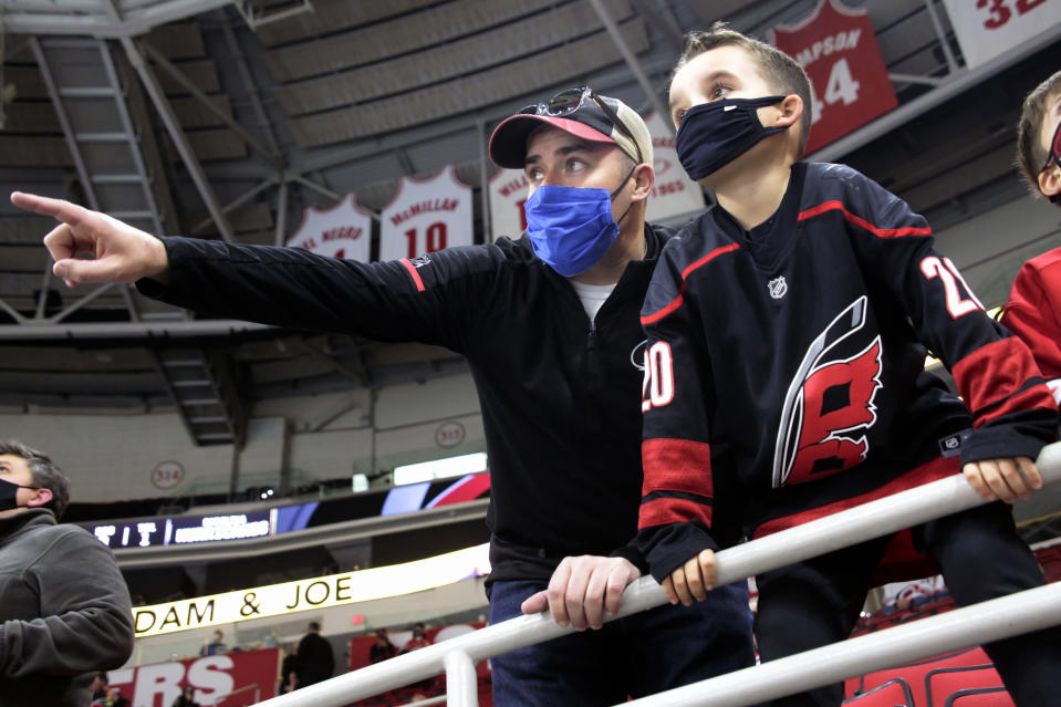 Derek DeYoung, left, points out players to his son Dominic DeYoung as the Carolina Hurricanes warm up before an NHL hockey game against the Detroit Red Wings in Raleigh, N.C., on Thursday, March 4, 2021. It is the first game where a limited number of fans have been allowed in PNC Arena to watch the team. (AP Photo/Chris Seward)