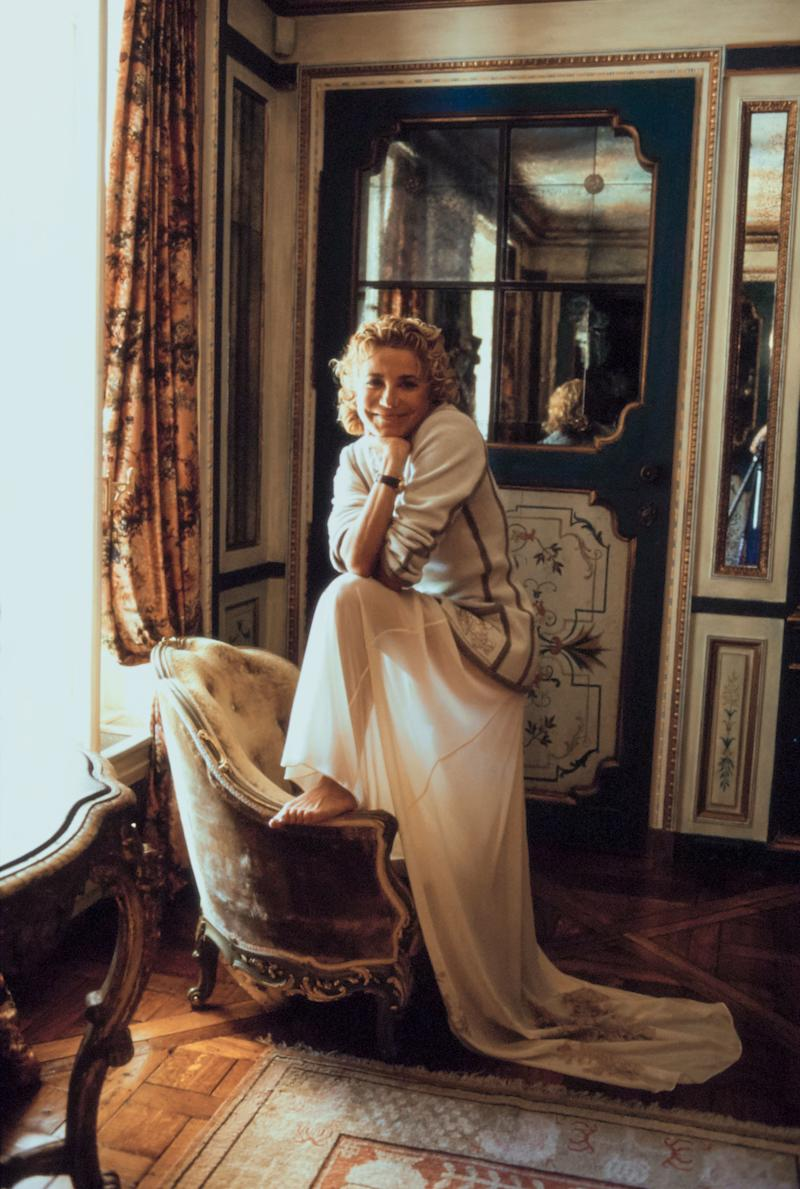 Laura Ungaro, wife of fashion designer Emanuel Ungaro, poses in their Paris, France, home with one foot on up on the arm of a chair and her elbows leaning on her knee. She is wearing a white sweater with a long white skirt. Hair by Kerry Warn at John Frieda using John Frieda products. Makeup by Alan Milroy for Faces.