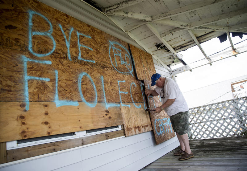 Billy Ezzell takes down boards covering windows after Hurricane Florence in Carolina Beach, N.C., Sept. 17, 2018. (Eric Thayer/The New York Times)