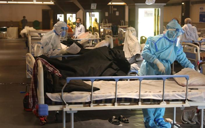 Doctors examine patients inside a Covid-19 care centre and isolation ward facility near a Hospital in New Delhi. Around fourteen private hospitals in Delhi, have been turned into fully Covid-19 treatment facilities due to extreme rise in cases - RAJAT GUPTA/EPA-EFE/Shutterstock