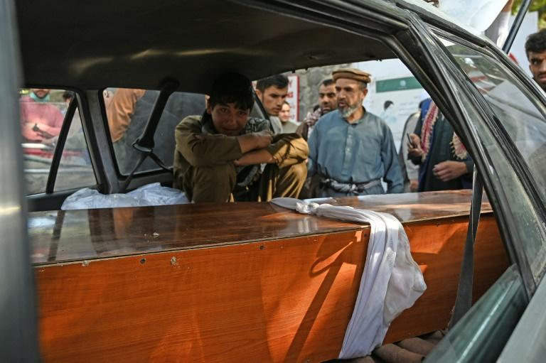A relative mourns inside a car next to the coffin of a victim of the August 26 twin suicide bombs, which killed scores of people including 13 US troops outside Kabul airport (AFP/Aamir QURESHI)