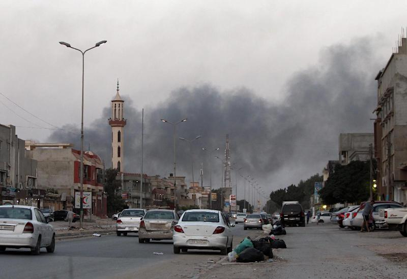 Smoke billows from buildings during clashes between Libyan security forces and armed Islamist groups in the eastern coastal city of Benghazi on August 23, 2014