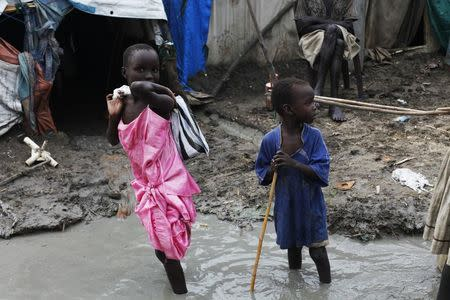Children walk through mud in the internally displaced persons camp inside the United Nations base in Malakal