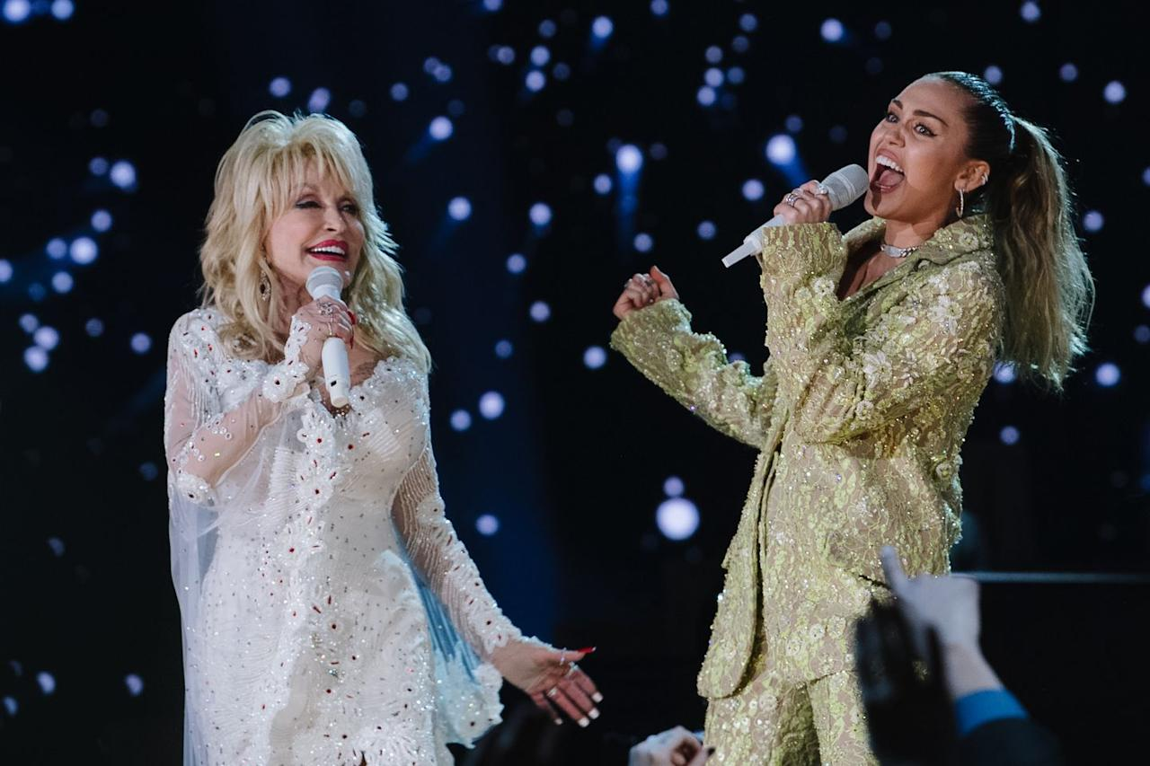 "<p>Country legends Dolly Parton and Billy Ray Cyrus are so close that the ""Achy Breaky Heart"" singer decided to make Dolly the godmother of his daughter Miley. Despite being a music icon, Dolly is Miley's number one fan, and the feeling is mutual; Miley sang a stunning rendition of <a href=""https://www.youtube.com/watch?v=aiKXGLqw-bU"" target=""_blank"">""Jolene""</a> (one of her favorite songs) during the 2019 Grammys as a tribute to her godmother.</p><p>Both women have a lot in common, from their unique senses of style to their love for country music. And Dolly sees a lot of herself in her goddaughter, having been somewhat of controversial figure herself when she was younger. ""Back in the day, doing my own things my own way, and dressing sexy and showing my cleavage and all that, I got a lot of criticism,"" Dolly <a href=""https://people.com/celebrity/dolly-parton-defends-miley-cyrus-people-thought-i-was-trashy/"" target=""_blank"">shared</a>. ""[Miley's] a smart girl. She had to go to extremes to get her point across. I think she got the point across."" </p>"