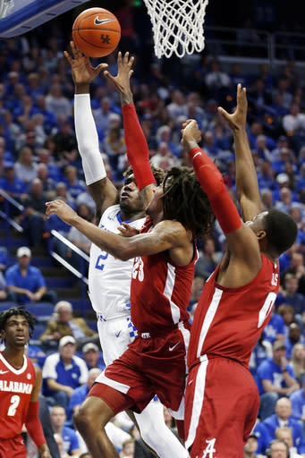 Kentucky's Kahlil Whitney, left, shoots while pressured by Alabama's John Petty Jr. and Javian Davis, right, during the first half of an NCAA college basketball game in Lexington, Ky., Saturday, Jan 11, 2020. (AP Photo/James Crisp)