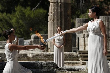 Greek actress Menegaki, playing the role of High Priestess, passes the Olympic flame to a priestess during a lighting ceremony of the Sochi 2014 Winter Olympic Games at the site of ancient Olympia