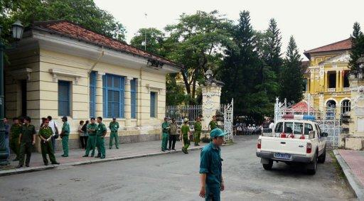 """Policemen and security staff stand outside the main entrance gate of Ho Chi Minh City's People's Court. A court in southern Vietnam jailed three bloggers Monday for """"anti-state propaganda"""" at a brief but dramatic hearing, prompting calls from the United States and EU for their immediate release"""