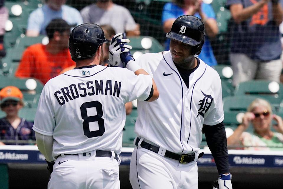 Detroit Tigers right fielder Robbie Grossman is greeted by Jonathan Schoop after hitting a solo home run during the first inning of the first baseball game of a doubleheader against the Minnesota Twins, Saturday, July 17, 2021, in Detroit.