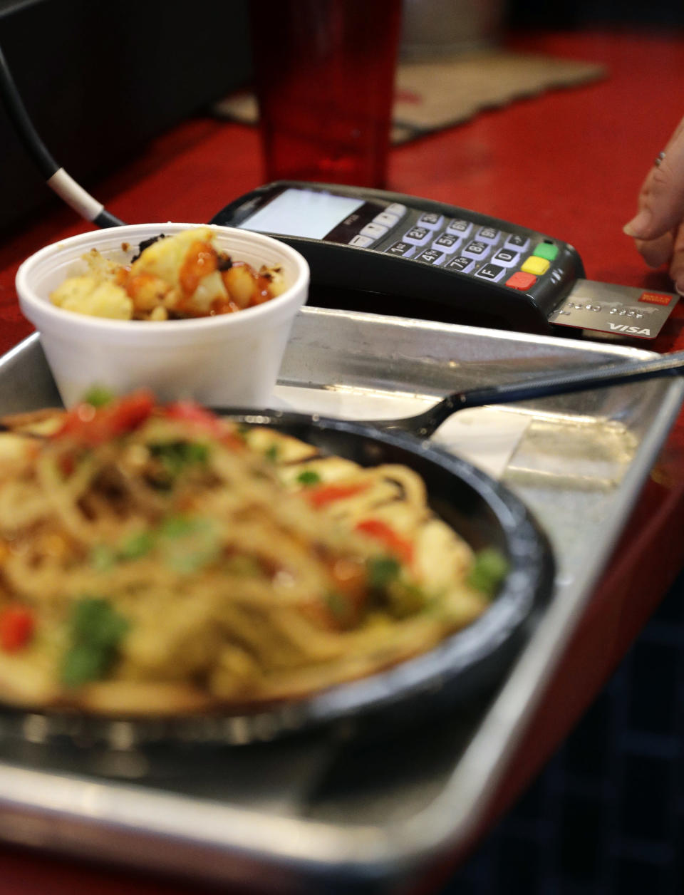 FILE - In this April 10, 2018, file photo, a customers uses a credit card machine to pay for food at Peli Peli Kitchen in Houston. Owner Thomas Nguyen had a change of heart after transitioning one of his three Peli Peli South African fine dining restaurants and his Peli Peli Kitchen fast casual location to a no-cash policy. (AP Photo/David J. Phillip, File)