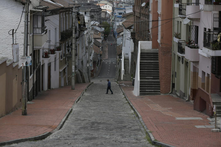 A downtown resident crosses a street free of pedestrians and traffic as a result of new lockdown restrictions due to the increase in COVID-19 infections, in Quito, Ecuador, Saturday, April 24, 2021. (AP Photo/Dolores Ochoa)